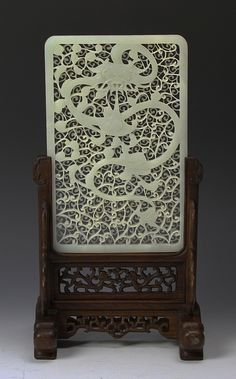 China, ROC period, jade screen, intricately carved with flowing designs and a fierce dragon figure, with wood stand. Height 8 3/4 in. Width 5 3/4 in.
