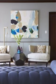 The geometric profile of the occasional table paired with the overscale abstract art resonates modern. The colorful palette of the art and accessories creates a softer, more approachable overall style.