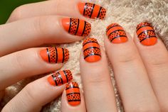 This striped and speckled orange and black mani is perfect for Halloween.