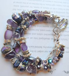 ~this new piece is stunning with funky artisan appeal and tons of bold beautiful vibrant stones  ~ features three strands, one of faceted lavender crystal, to deep ab treated purple crystal, to stack silver beads, then a stack of expensiveAB mystic treated faceted lapis lazuli, a faceted wheel of amethyst ,to the center of the silver sterling silver set bezel set faceted amethyst druzy,then a section of AB Crystal, to Blue hematite, faceted amethyst cubes, an ab treated crystal cubes of…