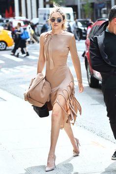 Gigi Hadid in a curve-skimming beige one-shouldered Jonathan Simkhai dress.