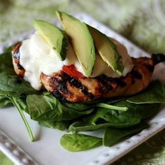 Grilled chicken breast with tomato, mozzarella, and avocado over baby spinach