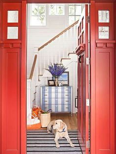 Bright red entry to a beauitful coastal home with a striped dresser as an eye-catching focal point.
