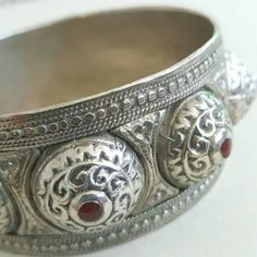 Traditional vintage bracelet from the Fez or Meknes region made in the ornate Chems O Qmar/Lune et Soleil or Sun and Moon style of embossing and doming the silver. This piece is especially nicely done with red enamel tipped domes (all intact) and sweet little hearts worked into the design.