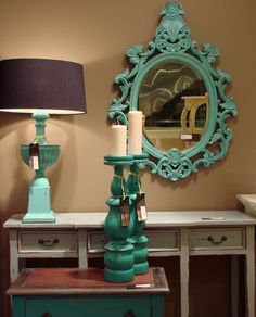 Chunky wooden candle sticks, an ornate mirror and an over-sized lamp..all in fresh shades of turquoise.