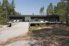 The Summer Villa VI is a low lying home located in a forested area of Kustaavi, Province of Western Finland. A long walkway of pale decking leads up to the