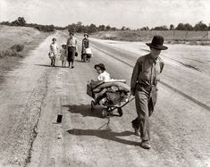 """June 1938. Pittsburg County, Oklahoma. """"Family walking on highway, five children. Started from Idabel, bound for Krebs. In 1936 the father farmed on thirds and fourths at Eagleton, McCurtain County. Was taken sick with pneumonia and lost farm. Was refused relief in county of 15 years' residence because of temporary residence elsewhere."""" Still, they didn't give up... they were Americans. The child is looking at what is probably the exposure sheet from the camera blown away. Pic by Dorothea…"""