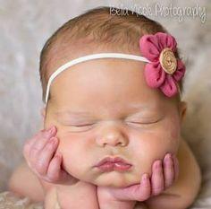 Newborn baby girl hands holding head. Bella Nicole Photography