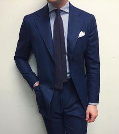 Navy suit, white shirt with navy dress stripes, dark grey knit tie