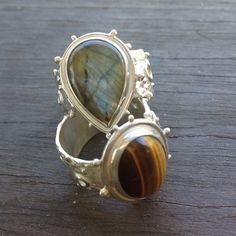 Pair of silver rings, cast shanks with hand made settings. Labradorite and tigers eye. By Gecko Skin Jewellery.