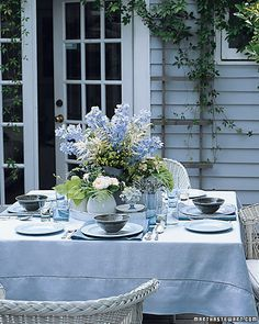 Assembling several small arrangements offers an easy, manageable way to tame a fresh-from-the-garden mix of roses, hydrangeas, delphiniums, lady's mantle, scented geraniums, and potato vine. A pitcher in the center gives height, while kitchen crocks (sugar bowls, eggcups) allow the inclusion of short-stemmed beauties. Using a monochromatic scheme of cool blues and contrasting the floral abundance with geometric place settings balances the romance with a little modernism.