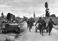 German troops from the 6th SS Mountain Division Nord advance past destroyed Soviet BT-7 tanks, 1941.