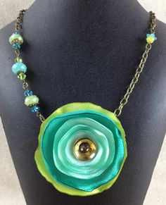 He encontrado este interesante anuncio de Etsy en https://www.etsy.com/es/listing/199790669/tri-color-green-fabric-flower-necklace