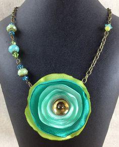 He encontrado este interesante anuncio de Etsy en https://www.etsy.com/es/listing/199790669/tri-color-green-fabric-flower-necklace