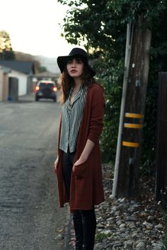 Style. Black leather-look pants, long wine red cardigan, stripy button up shirt and a hat. I'd change the hat type to fedora.