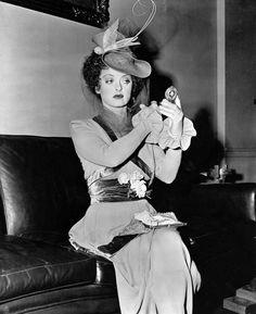 Bette Davis makes last-minute adjustments before going into the next scene in Mr. Skeffington 1944