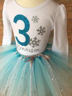 This sparkly snow delightful birthday outfit comes with a capped short or long sleeve shirt and a tutu skirt. The shirt is embellished with a blue, glittery 3 and silver, sparkly snowflakes. Her name can be added for $5 extra! The tutu skirt has 2 shades of blue, turquoise and light blue