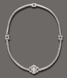 AN ART DECO DIAMOND NECKLACE   The old European-cut diamond line, centering upon an openwork old European, marquise and baguette-cut diamond plaque, mounted in platinum, (may be worn as two bracelets, each 7 ins., central plaque with concealed pendant hoop), circa 1920, necklace 14 ins.