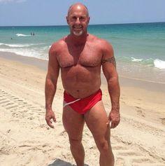 Bald Goateed SpeedoDad on a windy beach. The Speedo strings are blown sideways!