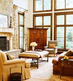 Those windows are a must for any dream home.  I love the comfort and elegance of this room.  I would want to curl up on that couch or in that arm chair in front of the fire and read a good book.