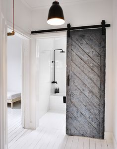 Bathroom with black reclaimed wood sliding barn door, in the