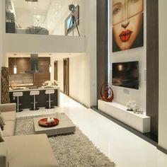 Sala de estar com tapete bege, painel de tv com quadro, cozinha integrada.