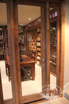A classic wine cellar door with sidelights creates a grand entrance into the space.