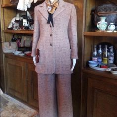 """Chanel Vintage Blush tweed Pantsuit, euro 38 Vintage 80's, authentic, Chanel pantsuit. Immaculate vintage condition. Pink and charcoal tweed with pink leather piped trim. Original Chanel Paris buttons. Chanel logo lined. Pants are a wide leg. Jacket is long with three Chanel stamped buttons. Euro size 38. Wool and silk. Very hip suit!  Pants- 30"""" inseam (addl 2"""" option to drop in hem)  43"""" waist to hem  27"""" waist/34"""" hip width  Jacket- 23"""" shoulder to sleeve 36"""" bust 34"""" waist 44"""" bottom 30""""…"""