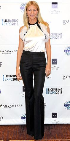 GWYNETH PALTROW in elegant black, slim but flared trousers and a silky white halter top.