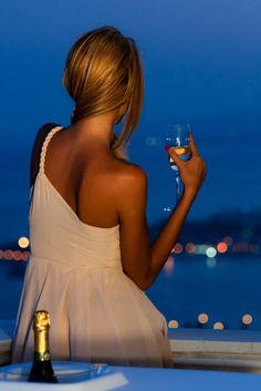 Woman standing on balcony at dusk, and holding a flute of Champagne.