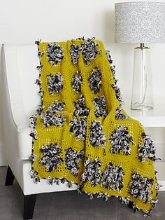 The whimsical floral texture of Bernat Fleurettes makes this fun blanket a cheerful addition to any room. (Yarnspirations)