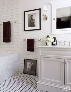 The tiles in a New York bath are by Nemo Tile Co., and the towels are by Restoration Hardware; the art includes a photograph by Machiel Botman, at top, and a Guzman portrait of Lambertson.  Pin it.