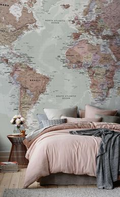 Not crazy about the map wallpaper but really like the light pastel pink and grey color scheme and different styled and different textured pillows on the bed.