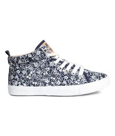 Dark blue/floral. High tops in cotton canvas with a printed pattern. Lacing at front, glittery tongue with appliqué, and a loop at back. Mesh lining, mesh