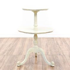This end table is featured in a solid wood with a distressed white paint finish. This shabby chic style side table has 2 tiers, carved pedestal, and tri-base with carved cabriole legs. A whimsical piece that's perfect for displaying plants! #shabbychic #tables #endtable #sandiegovintage #vintagefurniture