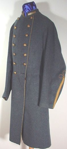 Confederate Officer's Frock Coat. Double breasted cadet gray coat is made of kersey wool imported through the blockade from England. Yellow piping around upper collar seam and front edges. The single strip of gold braid sewn to each side of collar and the coat's yellow piping denote it as belonging to a Second Lieutenant of Cavalry. Yellow wool strip from cuff to elbow outlined with gold bullion braid ending in a trefoil. Staff officer's buttons.