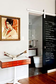 Raising the Roofbeams in Williamsburg - NYTimes.com: The guest bathroom, which has a tub, is on the mezzanine, a floor down from the guest room. The sliding door doubles as a blackboard. The woman in the painting is Mr. Goicolea's grandmother.