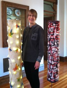 """P J Bergin with her abstract art wall hangings to the Glow Tubes™ series: freestanding, 3-dimensional installations featuring a multi-colored studio-dyed, wool felt and silk chiffon """"sleeve"""" with metallic accents.    A life-size metal floor pedestal supports the seamless felt sleeve and its battery-powered, cool LED interior lighting. The LED's provide pinpoints of accent lighting from within. Each Glow Tube™ includes its own timer.  www.FeltInHand.com"""