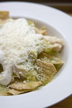 Chilaquiles Verdes (Corn Tortillas cut in quarters and fried then topped with chicken and green chile sauce) Toppings your choice.  See more at website.