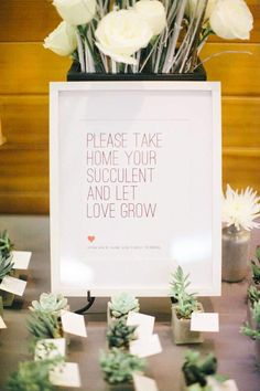 Small green plant wedding favors under a sign for guests at the reception.