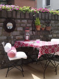 brings colour to her outdoor dining nook by attaching inexpensive indoor-outdoor fabric to the table with a staple gun. She also adds playful bolster pillows to the metal chairs that match the table cloth