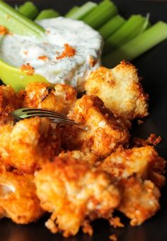 A plate of breaded buffalo cauliflower with a small bowl of ranch dipping sauce and raw celery sticks behind.