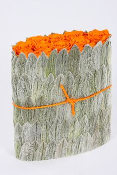 Orange roses enclosed in leaves of lamb's ear. The orange string is key. By Christian Tortu.