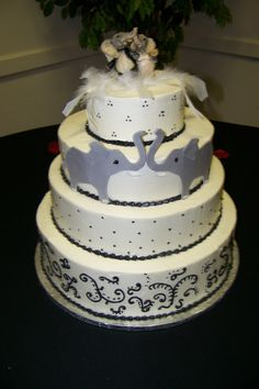 Black and white wedding cake with scroll piping, black dots, white feathers, elephants and ceramic elephant bride and groom topper