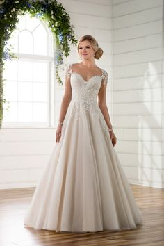A-line wedding dress idea - vintage elegance meets soft romance in this illusion sleeve wedding dress- lace detailing works its way down the sleeves before being accented with pearl buttons. Style D2253. Explore more designs by @essensedesigns at @weddingwire!