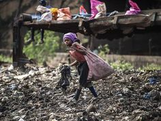 A girl sifts through garbage at a dumping site in Maputo, Mozambique
