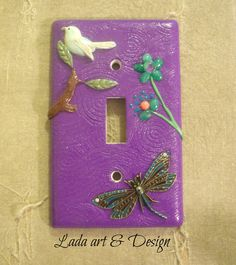 Nature Switch Plate Cover  A really cute addition to any room. A purple swirly background with bits of nature on it. A brass dragonfly flies up to a bird on a branch. Real gemstone flowers are on the side. Fits a standard light switch and comes with screws.