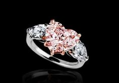 pink heart-shaped diamond flanked by 2 colorless pear-shaped diamonds mounted on rose gold and platinum. Heart Shaped Diamond Ring, Square Diamond Rings, Pink Diamond Ring, Black Diamond Studs, Silver Diamonds, White Gold Rings, Diamond Pendant, Diamond Jewelry, Diamond Earrings