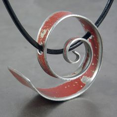 """This pendant was hand made using vintage car metal. All the original car paint has been left intact and unaltered. The red is from a 63 Toyota Land cruiser.This pendant measure approx 1 1/8"""" in diameter and is hung on leather cord with a sterling silver clasp."""