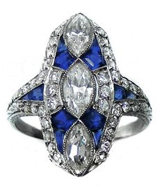 Diamond and sapphire panel cluster ring, three central marquise diamonds with calibrй sapphires between, diamond line border, sapphire and diamond shoulders. S.J. Phillips Ltd.